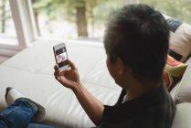 Homme utilisant un téléphone portable dans le salon à la maison — Photo de stock