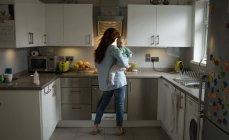 Mãe segurando sua menina na cozinha em casa — Fotografia de Stock