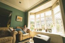 Homem segurando o controle remoto de televisão no sofá na sala de estar em casa. — Fotografia de Stock