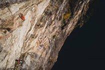 Entschlossener Bergsteiger erklimmt felsige Klippe — Stockfoto