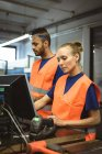 Двох працівників, що працюють на комп'ютері заводі — стокове фото