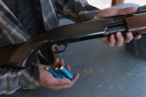 Mid section of man loading bullet into shotgun — Stock Photo