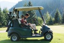 Pai e filho sentados no carrinho de golfe em um dia ensolarado — Fotografia de Stock