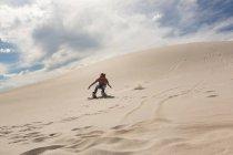 Woman sandboarding on sand dune at desert — Stock Photo