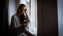 Adolescente réfléchie utilisant le téléphone mobile à la maison — Photo de stock