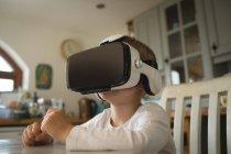 Крупный план мальчика, испытывающего виртуальную реальность гарнитуры на кухне дома — стоковое фото