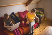 Семья на диване с использованием мультимедийных устройств в домашних условиях — стоковое фото