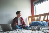 Young man sitting on bed with notebook and laptop at home. — Stock Photo