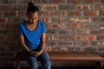Menina pré-adolescente usando smartphone no escritório . — Fotografia de Stock