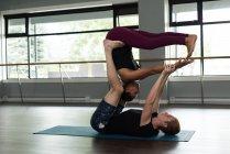 Ajuste de homem e mulher praticando acroyoga no estúdio de fitness. — Fotografia de Stock
