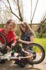 Мати і дочка, ремонт велосипедів разом на задньому дворі — стокове фото