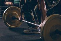 Низкая секция мускулистого человека, тренирующегося с штангой в фитнес-студии — стоковое фото
