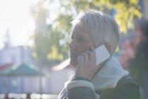 Вид збоку старші жінки говорять на мобільний телефон у сонячний день — стокове фото