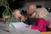 Father cleaning son with napkin while drawing with kids in living room at home. — Stock Photo