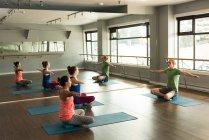 Formatore, aiutando le donne a praticare lo yoga a fitness studio. — Foto stock
