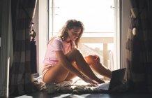 Frau benutzt Laptop an Glastür auf Decke zu Hause. — Stockfoto