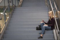 Teenage girl using mobile phone on staircase in university — Stock Photo