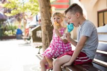 Sibling eating ice cream on bench during sunny day — Stock Photo