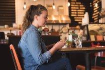 Frau, mit mobilen beim Frühstück am Tisch im café — Stockfoto