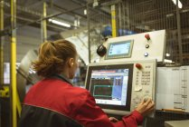 Female worker operating machine in factory — Stock Photo