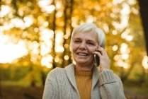 Close-up de mulher sênior sorrindo falando ao telefone no parque de outono — Fotografia de Stock