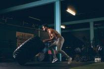 Мускулистый мужчина тренируется с тяжелой шиной в фитнес-студии — стоковое фото