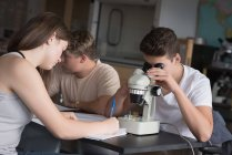 College students experimenting on microscope in laboratory at university — Stock Photo