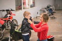 Mère préparant son fils pour faire du vélo dans le garage — Photo de stock