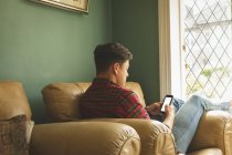 Man using mobile phone on sofa in living room at home. — Stock Photo