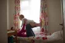 Mère jouant avec son bébé fille dans la chambre à coucher à la maison — Photo de stock