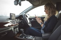 Bella dirigente femminile utilizzando cellulare in auto — Foto stock