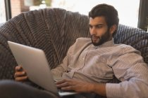 Man using laptop while relaxing on arm chair in coffee shop — Stock Photo