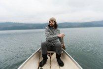 Homme pagayant canoë en rivière silencieuse — Photo de stock