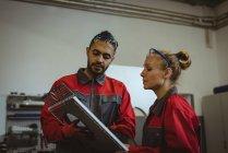 Zwei Arbeiter diskutieren über Maschinenbrett in Fabrik — Stockfoto
