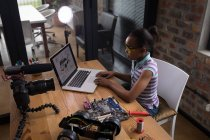 Pre-adolescent blogger girl using laptop while soldering circuit board of electric toy car in office. — Stock Photo