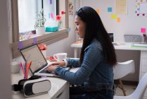 Diseñadora femenina usando laptop en estudio de diseño de oficina . - foto de stock