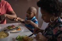 Garçon enfant d'âge préscolaire avec parents manger à table à manger à la maison — Photo de stock