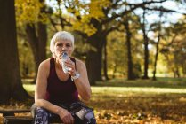 Senior woman drinking water in the park on a sunny day — Stock Photo