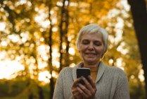 Sorrindo mulher idosa usando um telefone inteligente em um parque ao amanhecer — Fotografia de Stock