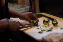 Cuoco unico che affetta il cetriolo con un coltello deba in cucina ristorante — Foto stock