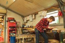 Young male carpenter using plane tool in workshop — Stockfoto