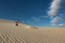 Femme sandboarding sur la dune de sable au désert — Photo de stock