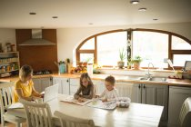 Siblings drawing while mother working on laptop in kitchen at home — Stock Photo