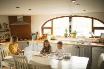 Frères et sœurs de dessin alors que mère travaillant sur ordinateur portable dans la cuisine à la maison — Photo de stock