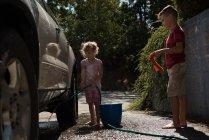 Frères et sœurs, laver une voiture au garage extérieur par une journée ensoleillée — Photo de stock