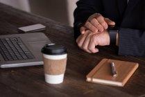 Section médiane d'homme d'affaires contrôle intelligent montre au bureau créatif — Photo de stock