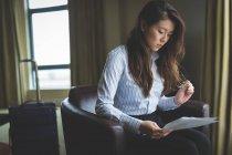 Geschäftsfrau Dokument zu lesen, während sitzt auf Sessel im Hotelzimmer — Stockfoto