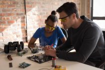Father teaching daughter about soldering iron in office. — Stock Photo