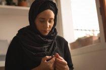 Mulher muçulmana rezando com grânulos de oração em casa — Fotografia de Stock
