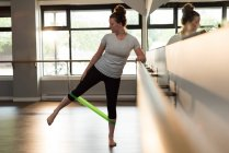 Woman exercising with resistance band in fitness studio. — Stock Photo